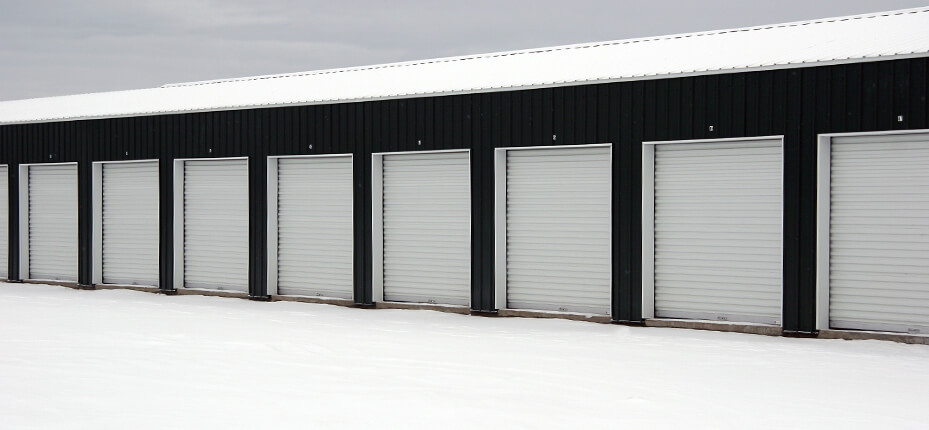 exterior of black commercial building with several rolling steel doors