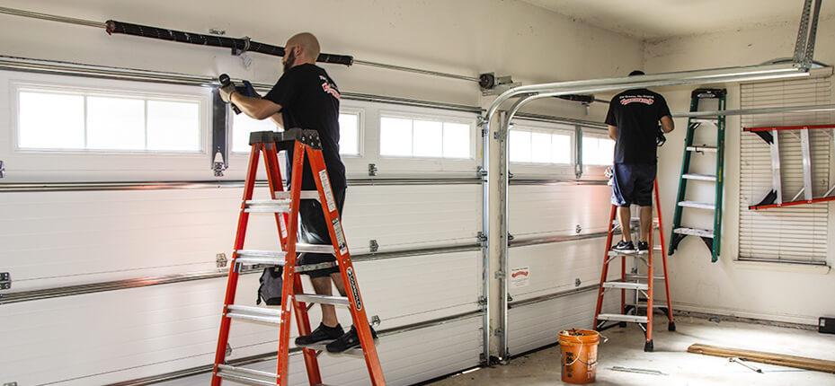 Two men on ladders work on garage door