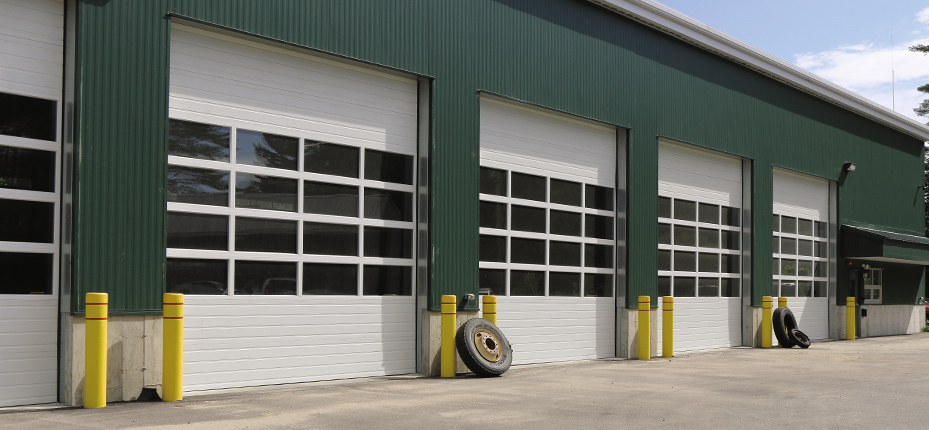 exterior of building with 4 white commercial garage doors
