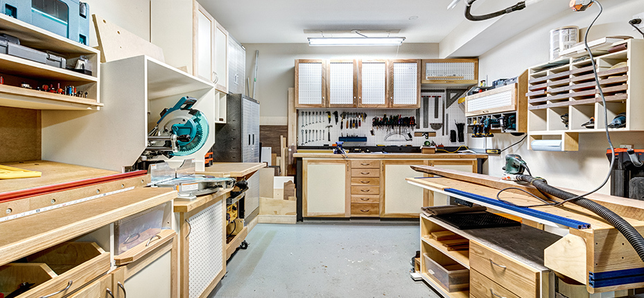 garage workshop with light tan and white cabinets