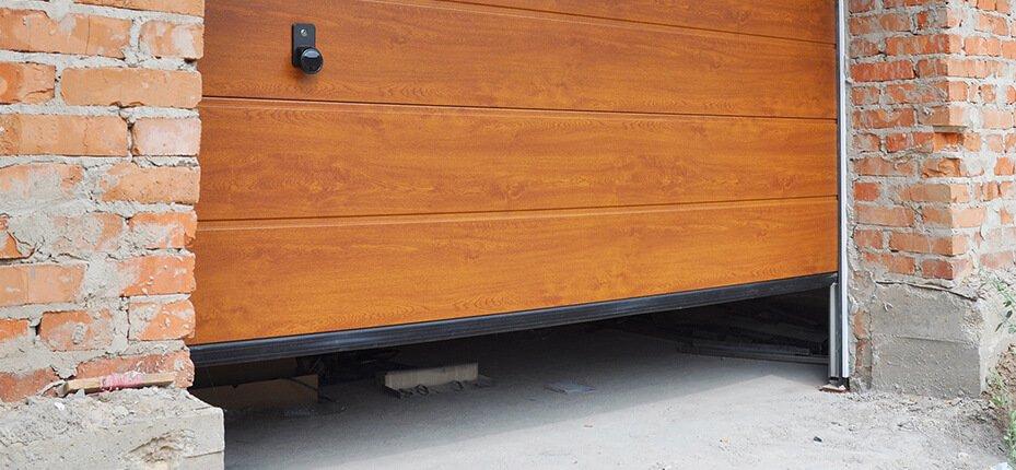 wooden garage door with black weatherstripping at bottom